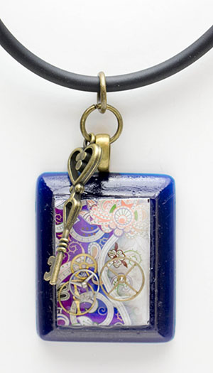 Dark blue resin pendant with watch cogs and brass key